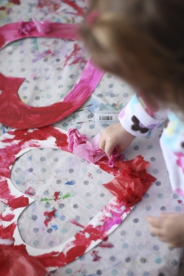 gluing tissue paper to a heart shaped wreath