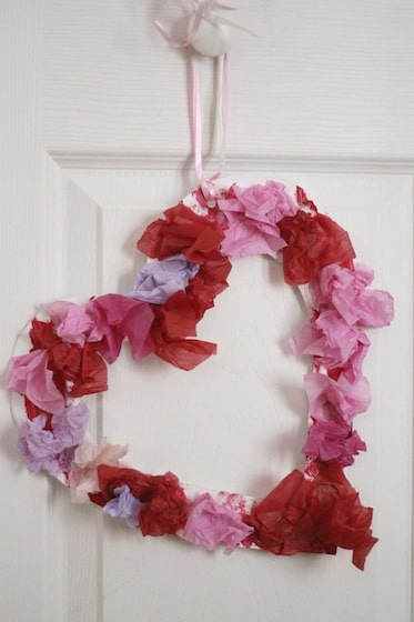 tissue paper Valentine wreath hanging from a door