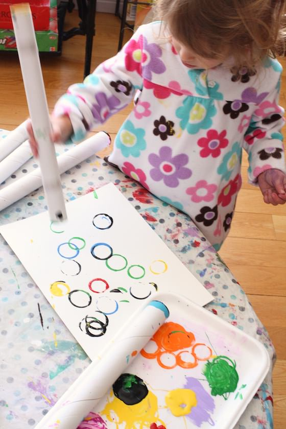 child stamping rings with cardboard roll