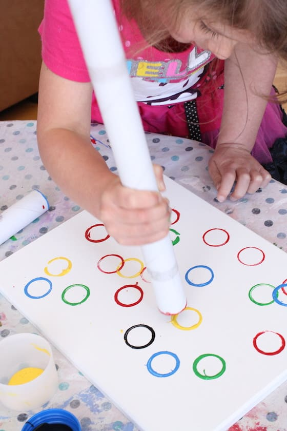 preschooler stamping Olympic Rings on canvas