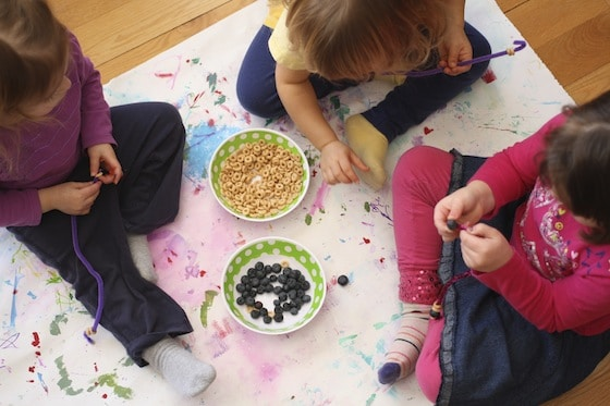 Gathered around a bowl, making bird feeders with cheerios and blueberries