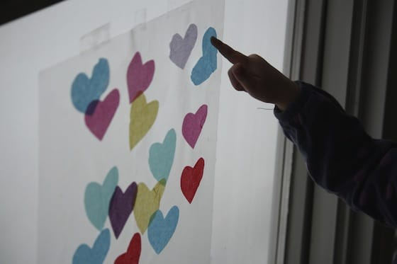 sticking tissue paper hearts to contact paper on a window