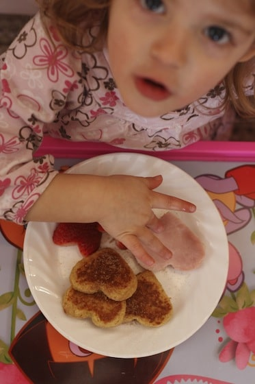 Child eating heart shaped French toast, ham and strawberries for lunch.