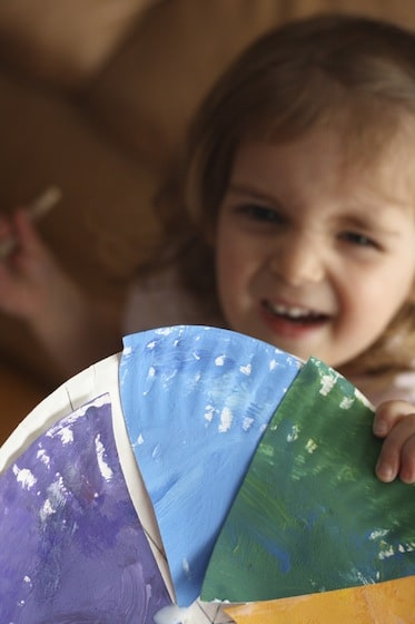 Toddler holding a paper plate colour wheel.