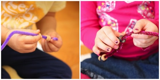 Threading cheerios and blueberries onto pipe cleaners
