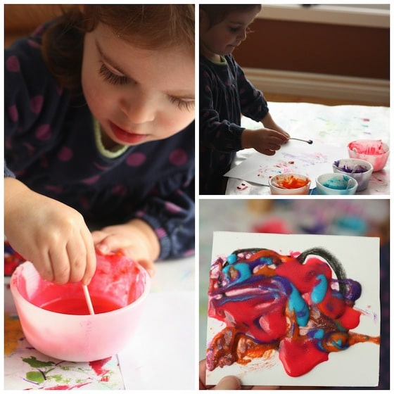 Child paints Valentines hearts with home-made puffy paint.