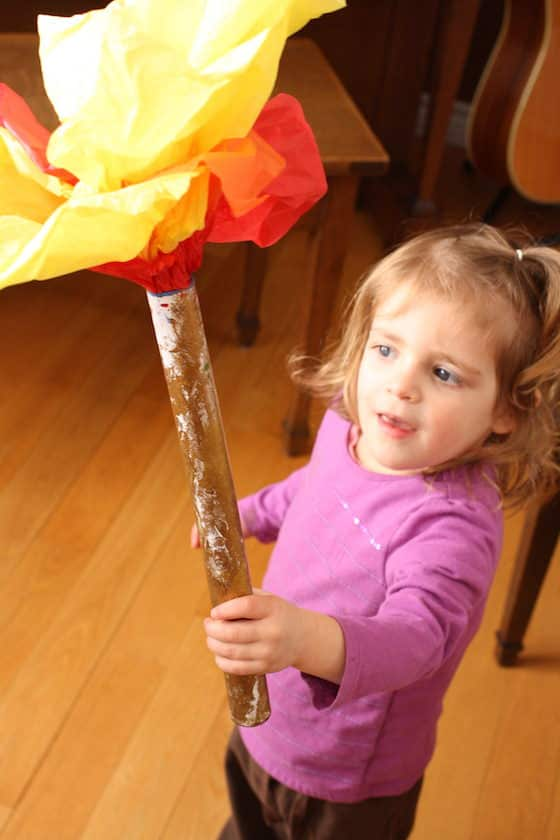 toddler holding Olympic torch made with cardboard roll and tissue paper