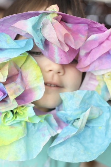 child peeking through easter wreath made with dyed coffee filters