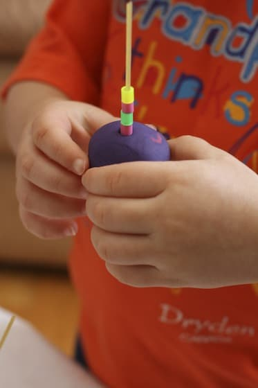 toddler playdough activity with beads and spaghetti