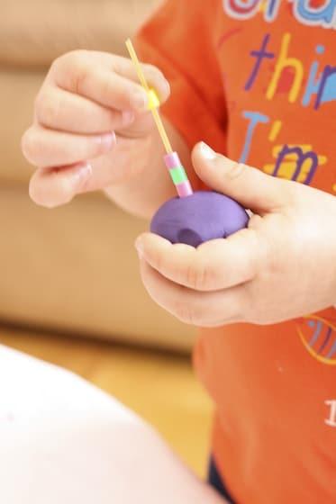 toddler threading beads onto spaghetti stuck into a ball of playdough