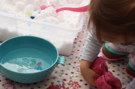 drying hands while playing with the snow sensory bin