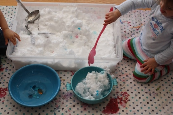 scooping snow out of the sensory bin and into bowls of water