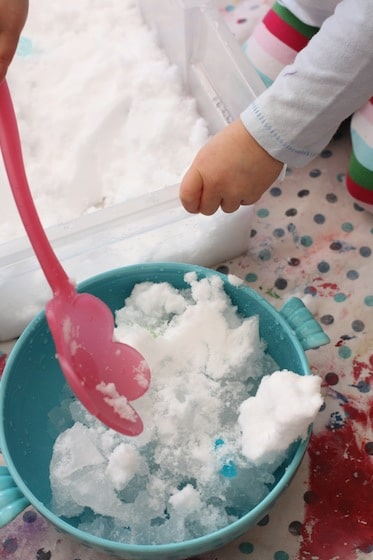 scooping snow into bowls of water