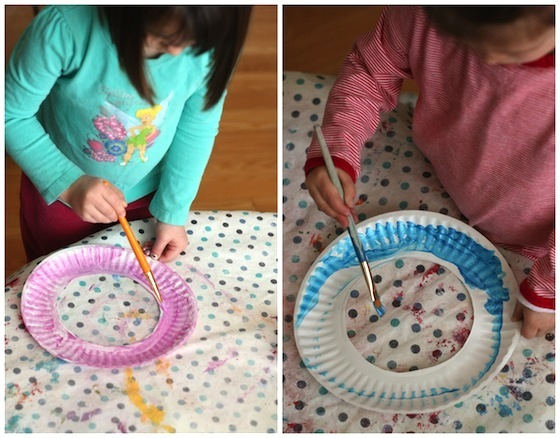 Painting paper plates to make an easter wreath.