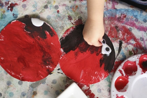 adding black paint and googly eyes to red paper plate