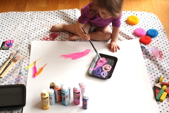 painting activities for toddler set out on a big cardboard canvas