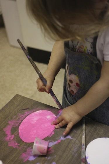 Toddler painting cardboard easter egg