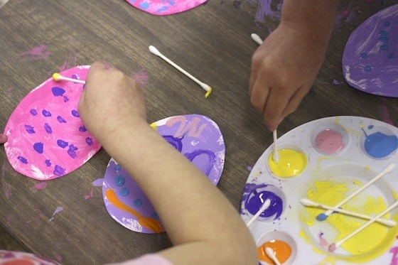 preschoolers painting with Q-tips on cardboard Easter Eggs