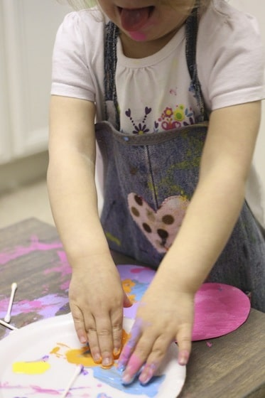 Toddler decorating easter eggs with her fingertips