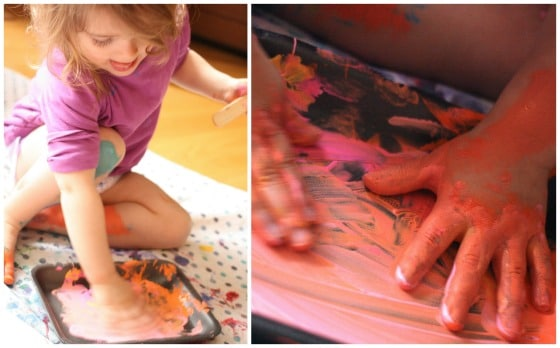 Toddler with hands in paint tray