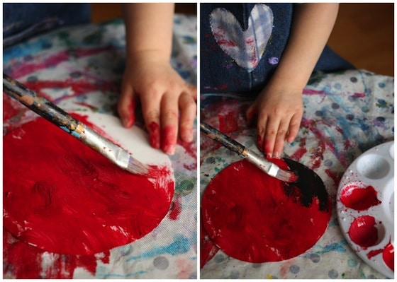 painting paper plates with red paint