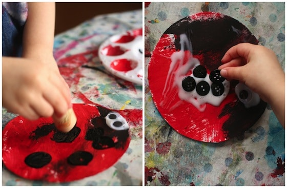 stamping black spots with a cork on red paper plate