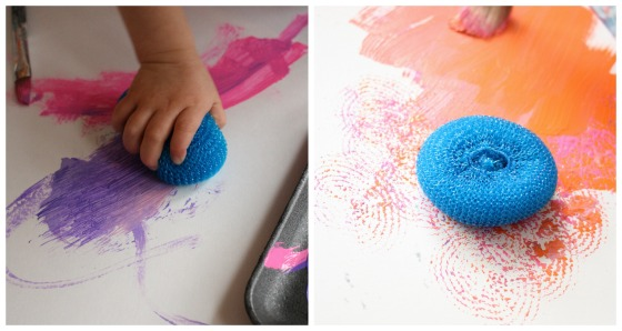 toddler painting with a dish scrubbie
