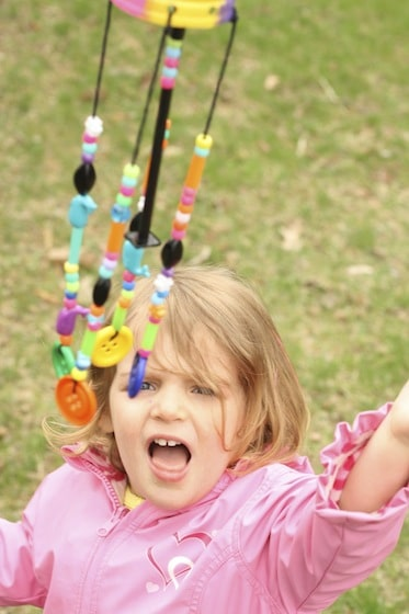child batting at DIY wind chimes