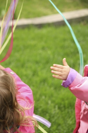 toddlers playing with windsock ribbons