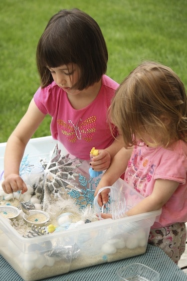 preschooler and toddler with hands in sensory bin