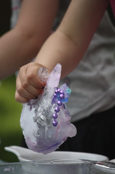 preschooler melting ice hand with salt and water