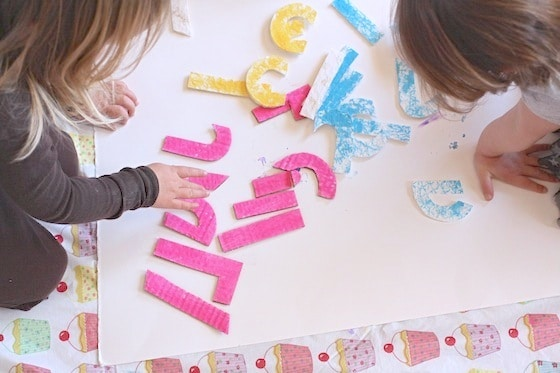 toddlers doing homemade name puzzle