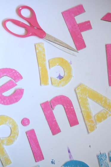 scissors and letters cut out for name puzzle