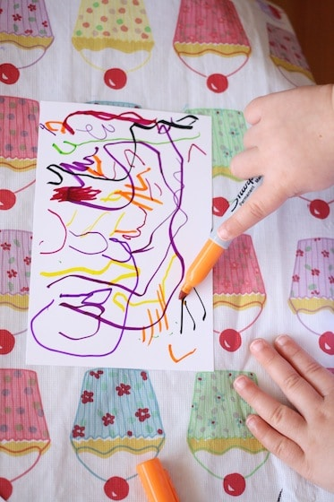 toddler making art on photo paper with a sharpies