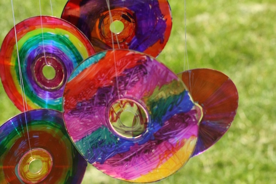 coloured CDS hanging from coffee can with fishing line