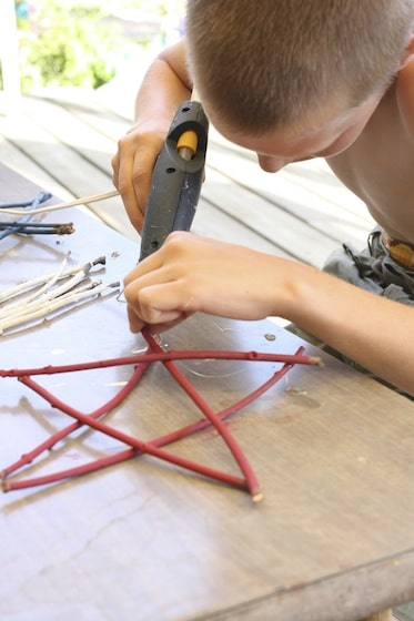 hot gluing red twig stars together