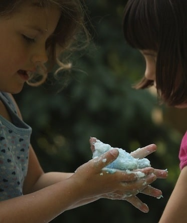 girls playing with blue clean mud