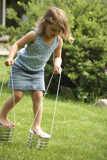 child walking on tin can stilts