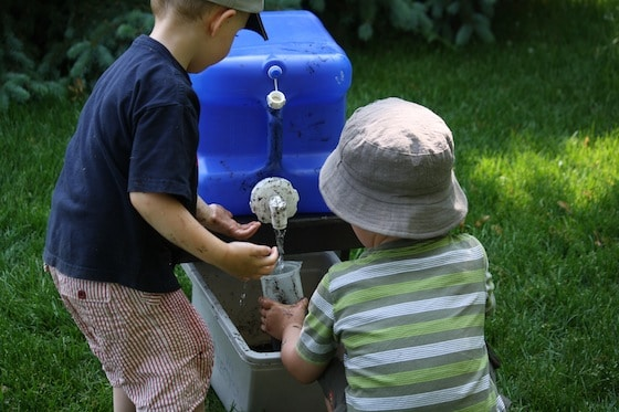 preschoolers filling measuring cup from blue camping jug in backyard