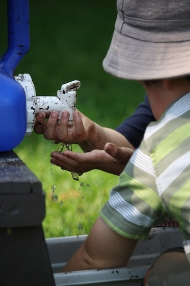 kids washing hands at blue camping water jug