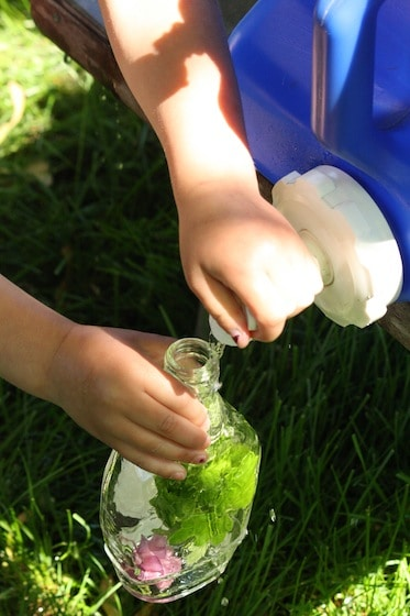 Child filling bottle with water from camping jug