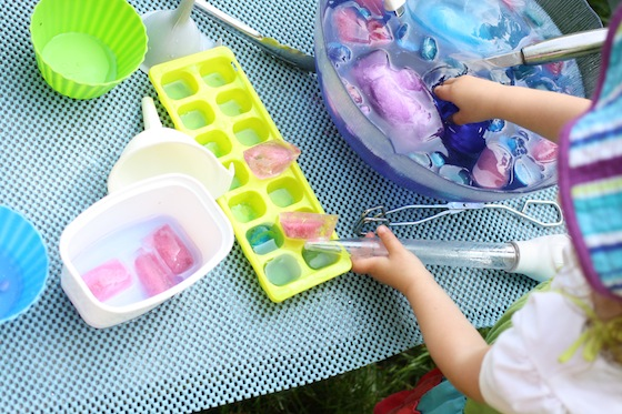 toddler putting coloured ice in ice cube tray