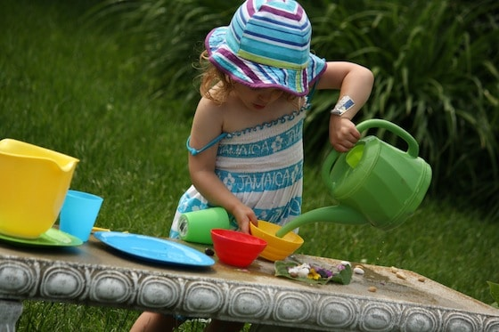 Toddler Pouring water out of green watering can, dishes for tea party