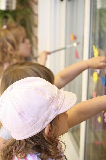 3 kids creating art on sliding glass door