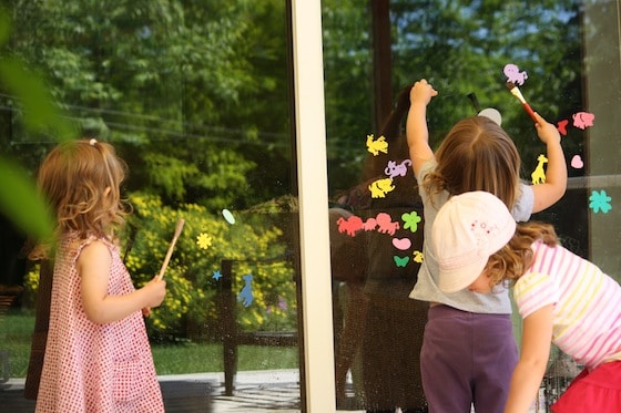 kids sticking foam shapes on window