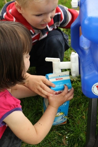 Kids filling empty milk carton with water from blue water carrier