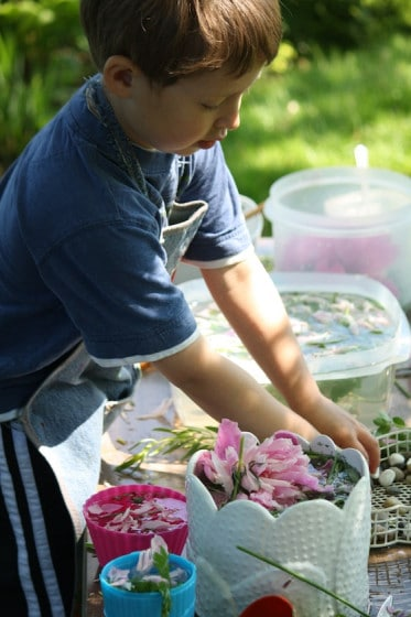 preschooler playing with water and flowers