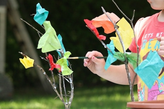 child making a fall tree with twigs and tissue paper