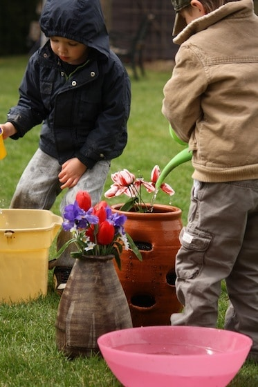 kids watering artificial flowers