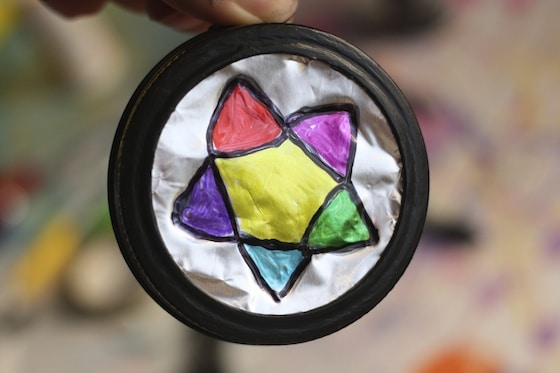 colourful star on tin foil in mason jar lid painted black